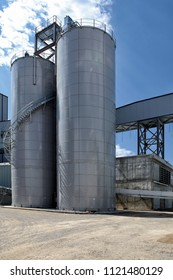 A group of granaries for storing barley and other cereal grains, located in a food processing facility.