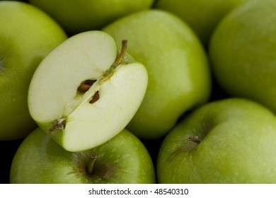 A group of Green Apples with a Cut Quarter