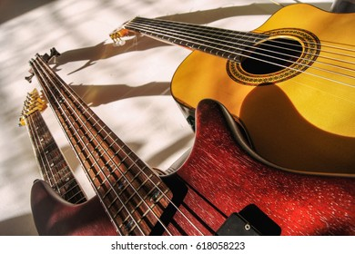 Group of guitars standing against a wall with beautiful colored sunlight shining on the instruments.