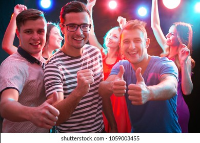 Group of guys dancing near the girlfriends in the night club
