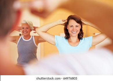 Group in a gym doing gymnastics with a fitness trainer