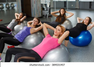 Group of Gym people exercising with Pilates fit balls. fitness, sport, training and gesture concept - group of smiling women showing thumbs up in gym. Group of people in a pilates class at gym
