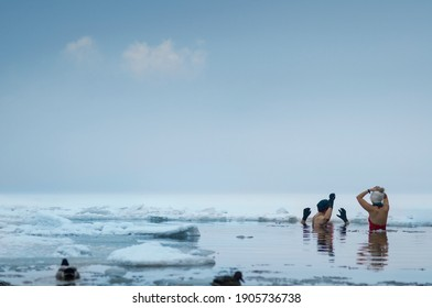 Group of half naked people standing in the freezing cold water, blue lake, ice floes and ducks in the foreground. Copy space.