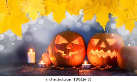 Group of Halloween pumpkin head jack o lantern and candles on dark wooden background , bokeh lights and autumn yellow maple leaves frame