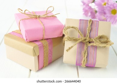 Group of handmade gift boxes with brown and pink paper wrap on white wood table with flowers