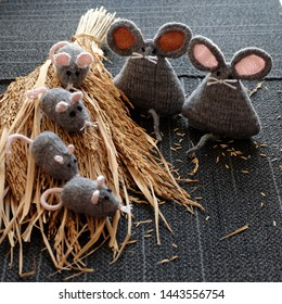 Group of handmade knit grey mouse on dry sheaf of rice plants with black background, handicraft rat from yarn so cute and nice, meaningful for gift or children toys