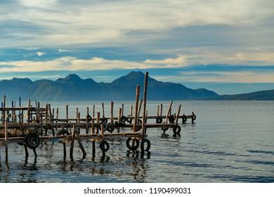 A group of handmade makeshift wooden docks during a tranquil morning at Lake Atitlan, Guatemala.