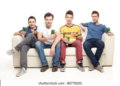group of handsome men sitting together on couch, watching television holding beers