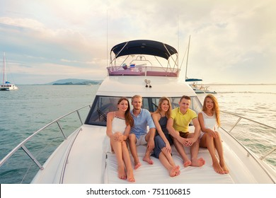 Group of handsome people relaxing on modern yacht and enjoying sunset. Luxury yacht cruise concept.