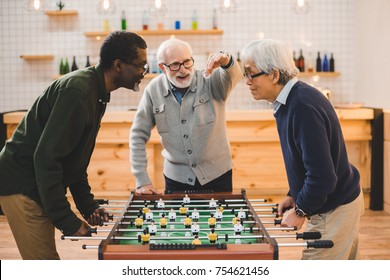 group of handsome senior friends playing table football at bar