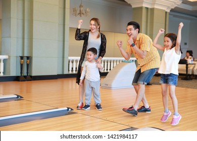 group of happiness asian family father, mother, son and daughter playing bowling in sport club with happy smiling face during holiday vacation