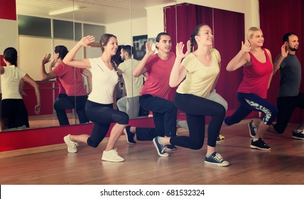 Group of happy adult people practicing with a trainer in a dancing school