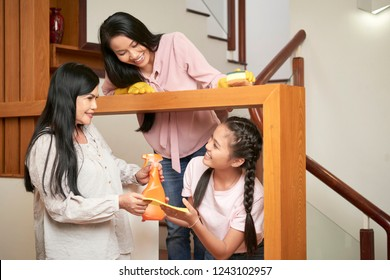 Group of happy adult and young women of family cleaning house together