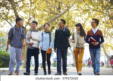 group of happy asian college students walking together in the campus