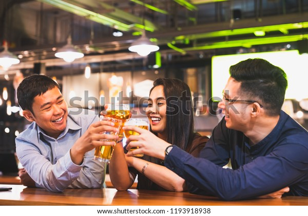 Group of happy Asian friends or office colleague coworkers celebrate toast beer pint together at pub restaurant or club. TGIF party, beer festival, team success event, or friendship lifestyle concept