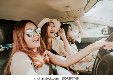 Group of happy Asian girl best friends laughing and smiling in car during a road trip to vacation.