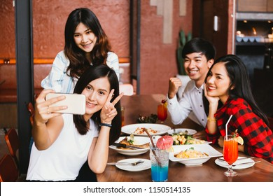 Group of Happy Asian male and female friends taking a selfie photo and having a social toast together in restaurant