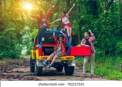 Group of happy asian young travellers on 4WD drive car off road in forest, travel and recreation concept.