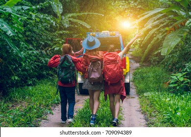 Group of happy asian young travellers walking outdoor with 4WD drive car off road in forest, young mixed race woman and man, travel and recreation concept.