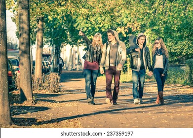 Group of happy best friends with alternative fashion look walking at the park - Hipster tourists having fun outdoors in sunny winter day - University students during a break hanging out together