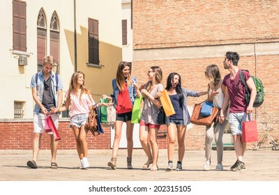 Group of happy best friends with shopping bags in city center - Tourists walking and having fun together at summer around old town - University students during break on sunny day - Bright warm filter