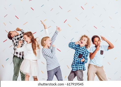 Group of happy boys and girls pretending to sing at a party