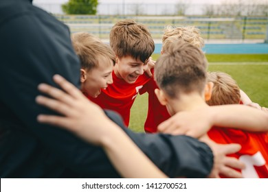 Group of happy boys making sports huddle. Smiling kids standing together with coach on grass sports field. Boys talking with coach before the football game. Happy children making sport