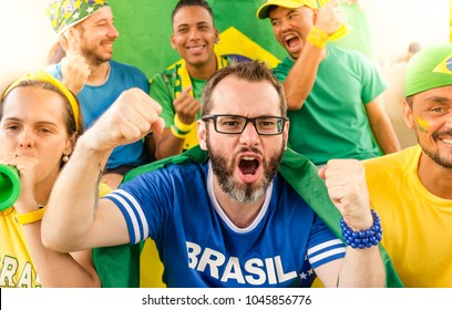 Group of happy brazilian soccer fans and friends at Stadium, Brazil.