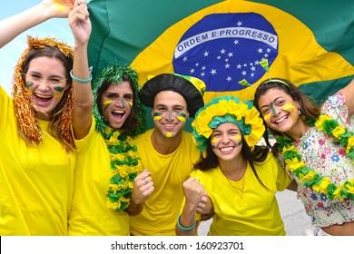 Group of happy brazilian soccer fans commemorating victory,with the flag of Brazil swinging in the air.