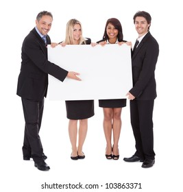 Group of happy business colleagues holding billboard isolated on white background