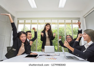Group of happy business people cheering in office. Celebrate success. Business team celebrate a good job in the office. Asian people.