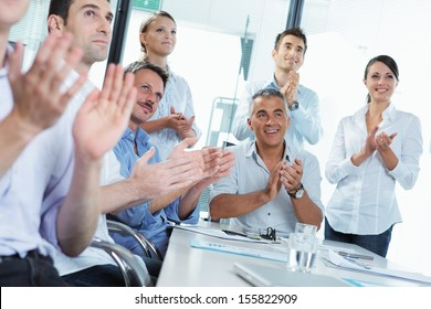 A group of happy business people clapping in a meeting