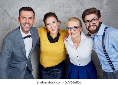 Group of happy business people posing standing together against concrete wall