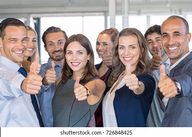 Group of happy business people showing sign of success. Successful business team showing thumbs up sign and looking at camera. Smiling businessmen and businesswomen cheering at office.