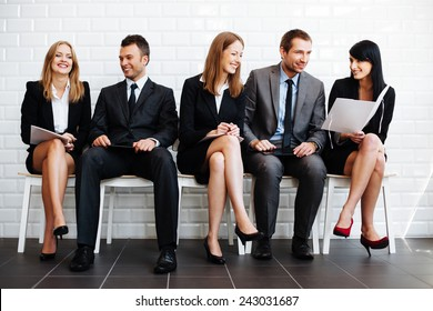 Group of happy business people sitting in waiting room
