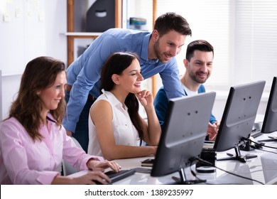Group Of Happy Business People Using Laptop Discussing At Workplace In Office