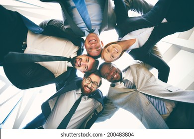 Group of happy businesspeople in suits standing head to head