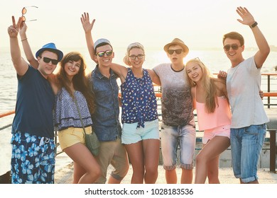 Group of happy carefree friends both young girls and men in casual clothes hanging out at the sunny summer seaside