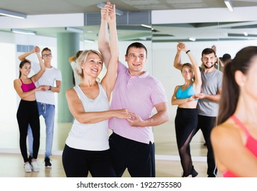 Group of happy cheerful positive smiling young adults dancing salsa in club