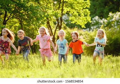Eine Gruppe glücklicher Kinder von Jungs und Mädchen laufen im Park auf dem Gras an einem sonnigen Sommertag . Das Konzept der ethnischen Freundschaft, des Friedens, der Freundlichkeit, der Kindheit