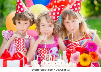 Group of happy children celebrating birthday. Kids having fun in spring garden