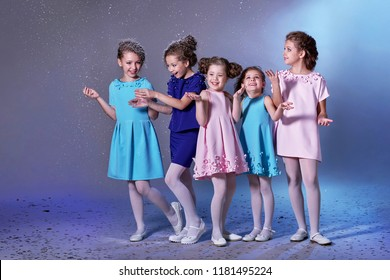 Group happy children in celebratory clothes for lady girls. Concept fashion, holiday, christmas, new year, x-mas, winter. Five kids in beautiful dresses enjoying snow on eve new year. Studio shot.