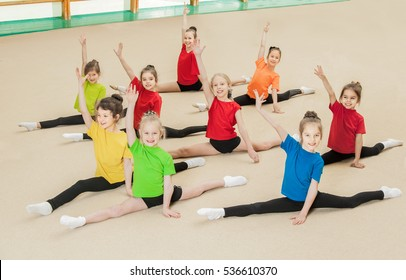 Group of  happy children doing exercise in gym