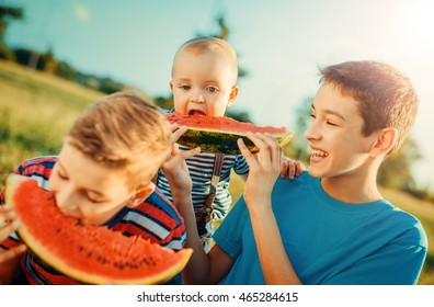 Group of happy children eating watermelon outdoors