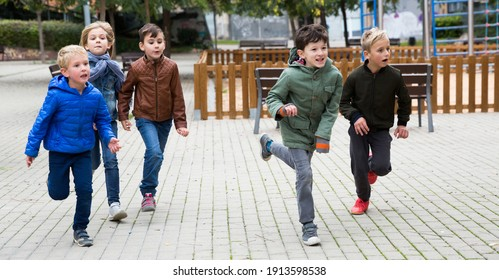 Group of happy children having fun together outdoors running on playground in autumn day