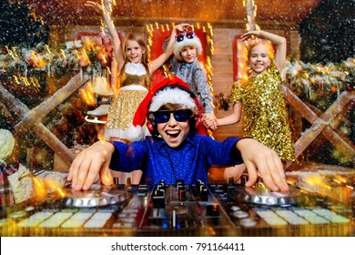 Group of happy children is having a party near the house of Santa Claus decorated with lights. Christmas party concept.