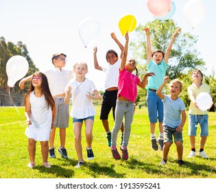 Group of happy children holding ballons and jumping together in park