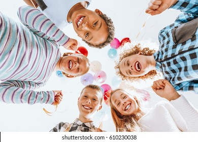 Group of happy children holding balloons and having fun
