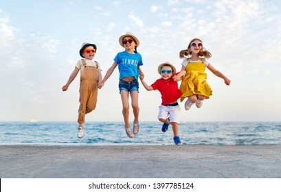 group of happy children jump by the sea in summer