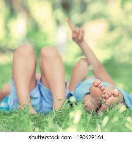 Group of happy children lying on green grass outdoors in summer park. Vintage filter photo